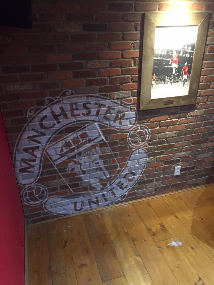 Wall logo airbrushed to brick facade